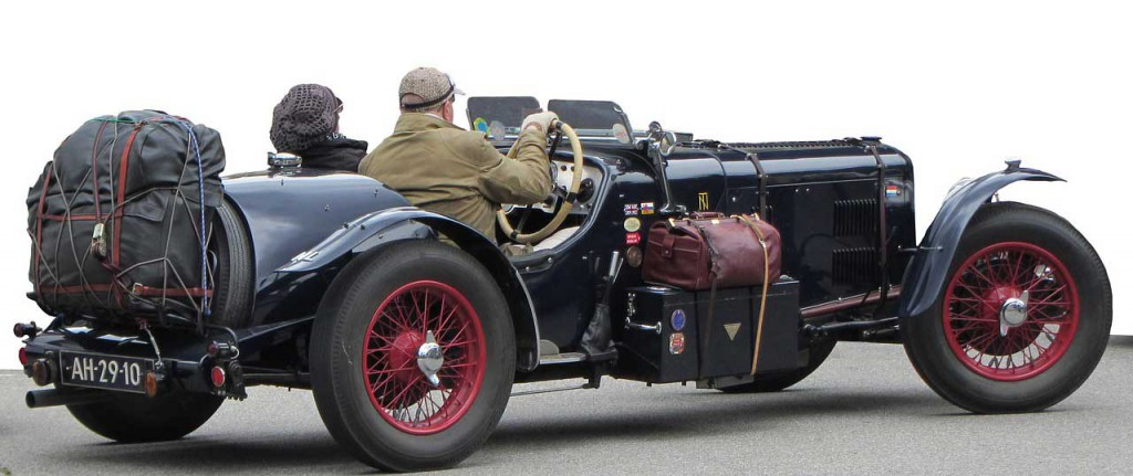 Retired couple starting off on a trip in an antique car with luggage onboard